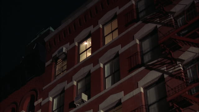 up angle of multi-story brick building with fire escape. alleys, windows. apartment buildings. middle class. - fire escape stock videos and b-roll footage