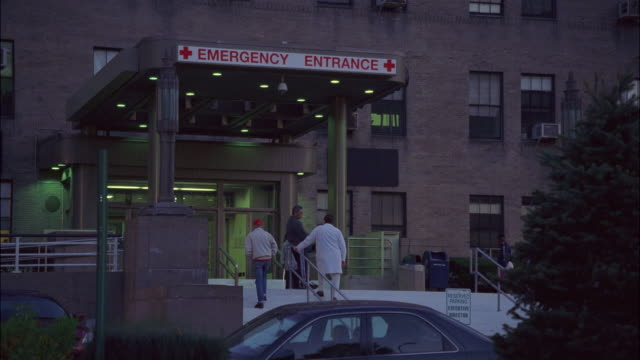 "wide angle of old brick hospital, emergency room entrance, staircase to parking lot, cars and jeeps parked. doctor talking with man, men, women enter, exit building. matching dx/nx 2253-032 to 2253-046.<p><a href=""https://www.sonypicturesstockfootage.com/ - www stock videos & royalty-free footage"