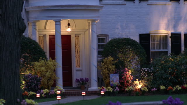"""pan left to right of white brick two-story house with black shuttered windows, small round balcony over front door. lamps lit inside house. upper class, suburban neighborhood. matching dx / dusk available.<p><a href=""""https://www.sonypicturesstockfootage.c - https点の映像素材/bロール"""