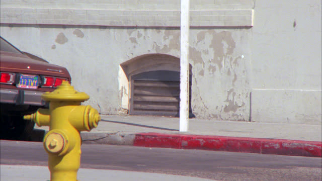 medium angle of yellow fire hydrant on street corner. building in bg. - fire hydrant stock videos & royalty-free footage