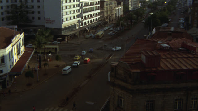 vídeos de stock, filmes e b-roll de high angle down of cars driving on city street, high rise buildings in nairboi, kenya. round tower, the kenya hilton hotel. - tempo real