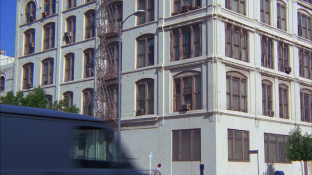 zoom in on basement window of multi-story apartment building with fire escapes on street corner. yellow  fire hydrant in fg. cars driving by in fg. - 非常階段点の映像素材/bロール