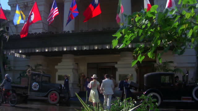 stockvideo's en b-roll-footage met wide angle of entrance to upper class hotel. flags including nazi swastika above overhang. classic cars and rickshaws driving by. people, sailors, women in dresses, kimonos walking by. world war ii. - nazisme