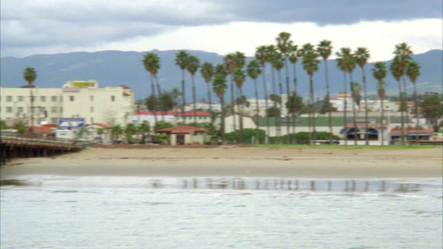 PAN RIGHT TO LEFT OF SANTA BARBARA COASTLINE OR BEACH TO PIER AND BOARDWALK WITH PEOPLE. COULD BE SMALL RESTAURANT, BAR, OR CAFE ON THE WHARF OR WATERFRONT. PALM TREES, SAND, WAVES. MOUNTAINS IN BG.