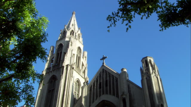up angle top of cathedral, church. see church steeple, cross on roof. pan down on entrance. see cars driving past cathedral. - steeple stock videos & royalty-free footage