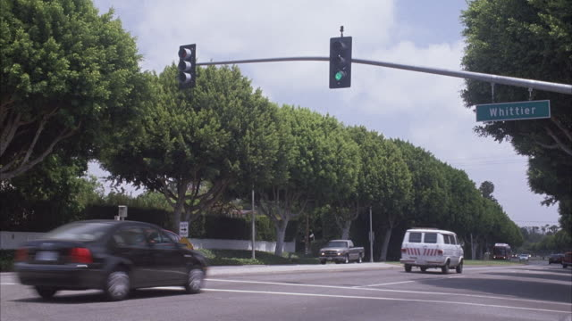 "wide angle of suburban area intersection. see green street sign hanging on stop light reading ""whittier."" cars driving through light. pan left to as red bus ""metro rapid"" passes cross street lined with jacaranda trees, purple blossoms. sunset boulevard th - 2004 stock videos and b-roll footage"