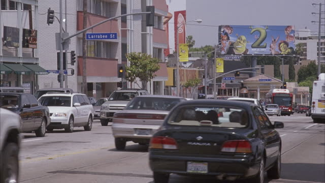 "wide angle of traffic filled city street in urban area. see blue street sign reading ""larrabee st"" and shrek 2 billboard. sunset strip. - sunset boulevard stock-videos und b-roll-filmmaterial"