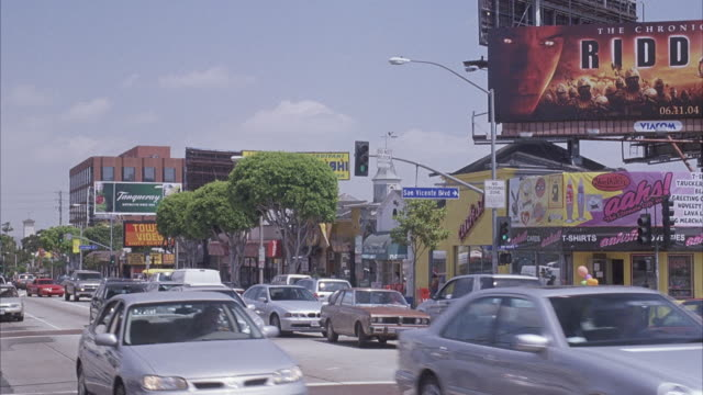 "wide angle of traffic filled city street in urban area. sunset strip. see billboard for ""the chronicles of riddick"" movie. track red bus driving right of pov. see hustler store on left and multi story building ""9000"" on right. - sunset boulevard stock-videos und b-roll-filmmaterial"