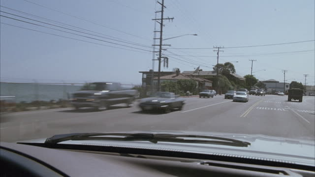 medium angle of silver car hood. see car traveling north on pacific coast highway with green hills on right ocean on right. see blue sky. see cars driving in opposite direction. pan back and forth. see beach houses lining street on left. - north pacific ocean stock videos & royalty-free footage