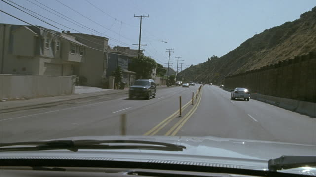 MEDIUM ANGLE OF SILVER CAR HOOD. SEE CAR TRAVELING NORTH ON PACIFIC COAST HIGHWAY WITH GREEN HILLS ON RIGHT OCEAN ON RIGHT. SEE BLUE SKY. SEE CARS DRIVING IN OPPOSITE DIRECTION. PAN BACK AND FORTH. SEE BEACH HOUSES LINING STREET ON LEFT.