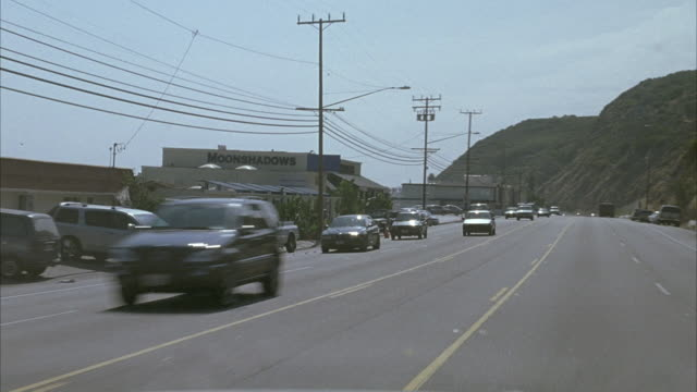medium angle of silver car hood. see car traveling north on pacific coast highway with green hills on right ocean on right. see blue sky. see cars driving in opposite direction. pan back and forth. see beach houses lining street on left. - north pacific stock videos & royalty-free footage