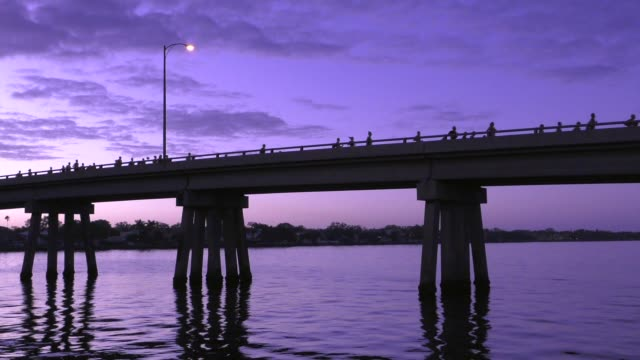 stockvideo's en b-roll-footage met runners head over bridge as sun rises - salmini