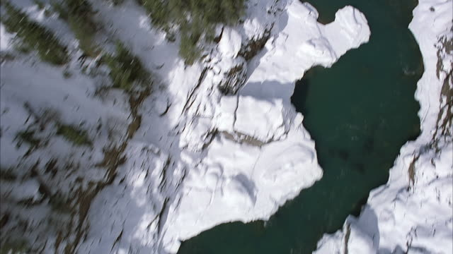 AERIAL BIRDSEYE POV OF PARTIALLY FROZEN RIVER IN SNOWY MOUNTAIN GORGE. COULD BE RAVINE OR VALLEY. SEE SNOW ON ROCKY TERRAIN, ICE, AND OPEN WATER. SEE SHADOWS FROM MOUNTAIN PEAKS. COULD BE PLATE. WINTER.