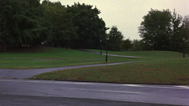 stockvideo's en b-roll-footage met medium angle of empty park. see black street lamps. see two lane road in foreground. see green nonconiferous trees. tracking shot of red 1981 chrysler fifth avenue  driving left to right. see car crash into street rail. see blood on front window. see shat - 1981