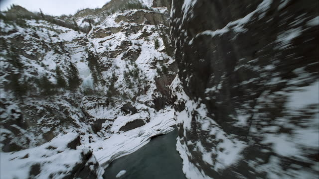 aerial of forward window pov from helicopter or airplane flying through mountain gorge in winter. see partially frozen river with ice and open water. see exposed rocks through snow and coniferous evergreen trees. could be canyon, ravine, or valley. could - frozen water stock videos & royalty-free footage