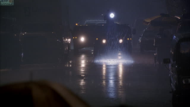 medium angle of new york city street. see military convoy driving toward camera. led by hummer with spotlight on roof. see reporters and soldiers walking across camera carrying umbrellas in heavy rain. - hummer stock videos & royalty-free footage