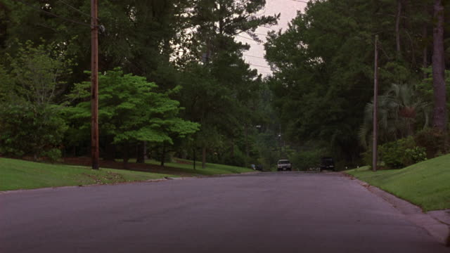 medium angle of two lane street in upper class residential neighborhood. see lush green trees flanking road. see tan buick electra estate wagon drive towards pov at left side of road. see speeding black 1993 cadillac fleetwood swerve around station wagon. - cadillac stock videos & royalty-free footage