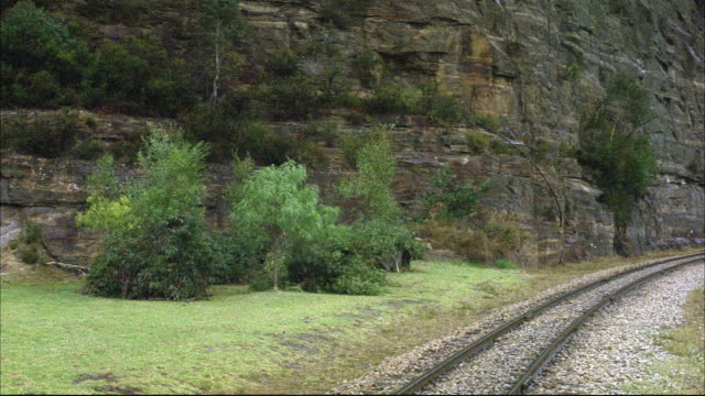 medium angle of railroad track with rock wall on left. see green grass and several trees at base of cliff. see black steam engine train enter pov. see steam rising from bottom of train. see steam fill pov. see boxcars through steam as train rolls out of p - c119gs stock videos & royalty-free footage