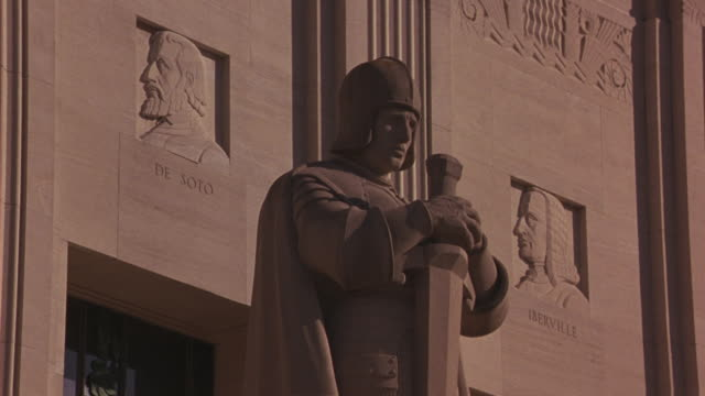 medium angle of statue in front of capitol building in baton rouge, louisiana. helmeted man holding sword. government buildings. - baton rouge stock-videos und b-roll-filmmaterial