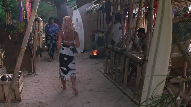 medium angle of small beach marketplace. see pacific islanders weaving palm leaves, carving small surfboard decorations, and making flower arrangements. see blond woman in bra and long skirt walk through market. - pazifikinseln stock-videos und b-roll-filmmaterial