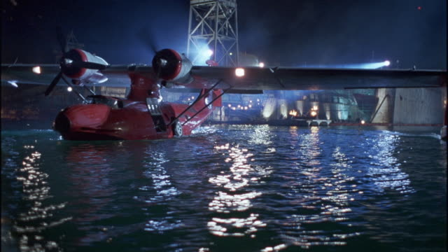 WIDE ANGLE OF RED SEAPLANE OR WATER PLANE TAXIING IN INDUSTRIAL HARBOR OR LARGE SEA PORT. CAMERA CIRCLES PLANE REVEALING MULTIPLE TOWERS, CRANES, BUILDINGS, LARGE SHIPS AND TANKERS, FIRES BURNING ON DOCKS. PROPELLER AIRPLANES, OCEAN.