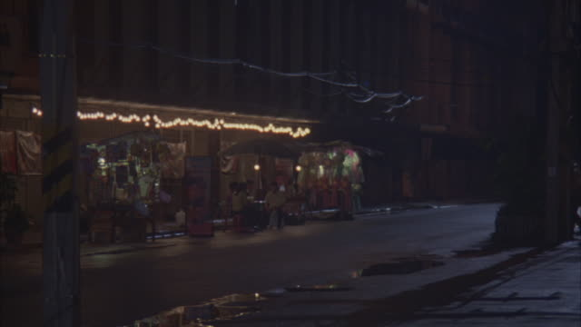 medium angle of city street lined with storefronts and restaurants. see buildings and hanging string of lights over vendor stands. see revamped jeep filled with gang members and dirt bike or motorcycle gang speed down street. camera pans left following bi - biker gang stock videos & royalty-free footage