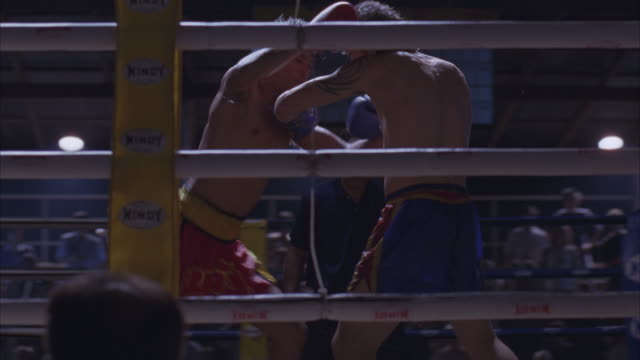 medium angle of kickboxers fighting in boxing ring from outside ring pov. men in ring punching and kicking each other. man on left in red shorts. man on right in blue shorts has tattoos. camera tracks around ring to follow boxers. see sweat flying off box - muay thai stock videos and b-roll footage