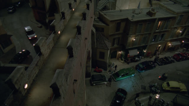 high angle down of walk way or bridge above street or alley in rome. cars parked on cobblestone street. people walk on sidewalk. cars drive on street. apartment buildings or shops. - vicolo video stock e b–roll
