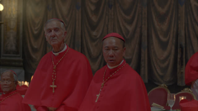 pan left to right of catholic cardinals sitting at tables and standing in dress robes. cardinals wear crosses. tables have lamps, books, and water glasses. could be meeting or conclave. rome. vatican. religious. - religious dress stock videos & royalty-free footage
