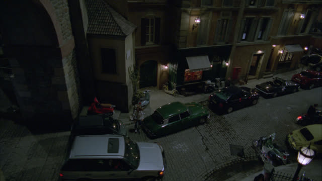 pan down from walk way or bridge over street or alley in rome. rope or cord hangs from brick walk. could be repelling rope. cars parked on curb of street. cobblestone. cars drive on street. shops with awnings. - vicolo video stock e b–roll