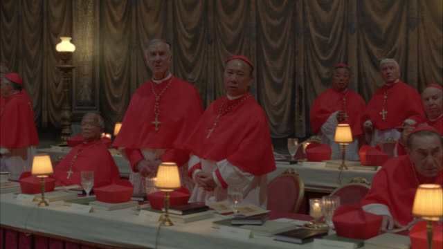 medium angle of catholic cardinals sitting at tables and standing in dress robes. cardinals wear crosses. tables have lamps, books, and water glasses. could be meeting or conclave. rome. vatican. religious. - religious dress stock videos & royalty-free footage