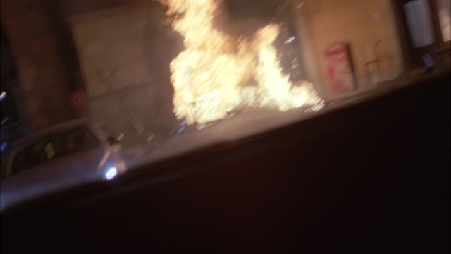wide angle driving pov straight back past car, volkswagen jetta a4, exploding into fire, flames and smoke. city street paved with stone setts. man gets out of nearby car. europe. could be bomb, terrorist attack or espionage. 48 fps. - volkswagen stock-videos und b-roll-filmmaterial