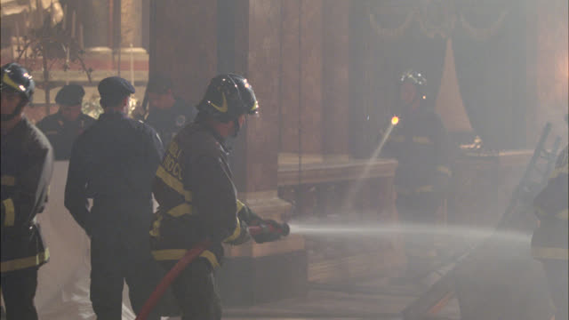 medium angle of fire fighters at crime scene. could be in church or chapel. men use flashlights in bg. chairs or rubble or debris in center of room. emts or paramedics cover dead body or corpse with white sheet. firefighters move church pews to reveal ela - rubble stock videos and b-roll footage