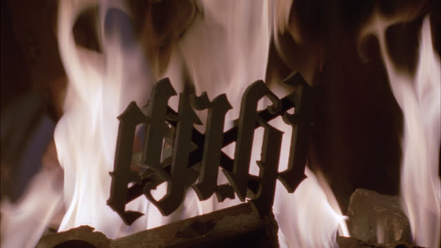 ZOOM IN ON BRANDING IRON, AMBIGRAM OF EARTH. FIRE AND FLAMES ON COALS.