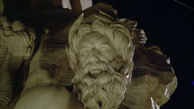 medium angle of sculpture or statue. light reflects onto sculpture. could be from water. could be fountain. could be fountain of the four rivers in piazza navona rome. - fontana struttura costruita dall'uomo video stock e b–roll