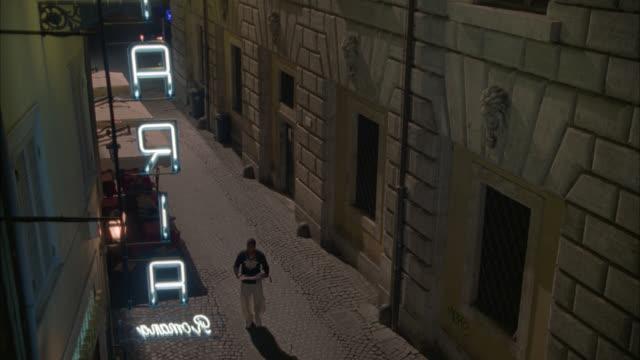 high angle down of man walking down cobblestone alley or street in rome reading book or pamphlet. neon sign for hotel or shop in fg. outdoor cafe or restaurant with awning visible below. - vicolo video stock e b–roll