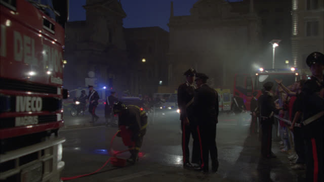 wide angle of police officers or carabinieri officers and firefighters outside of building. firefighters work with hose. could be fire. ambulances and fire trucks or fire engines with flashing lights. crowd stand behind barrier or barricade with carabinie - fire hose stock videos & royalty-free footage