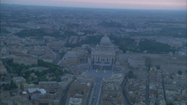 vídeos de stock e filmes b-roll de aerial of piazza san pietro (st. peter's square) and saint peter's basilica. catholic church. domed buildings. cities. shingled tile rooftops. plaza. multi-story apartment or office buildings. city skyline. europe. - basílica de são pedro