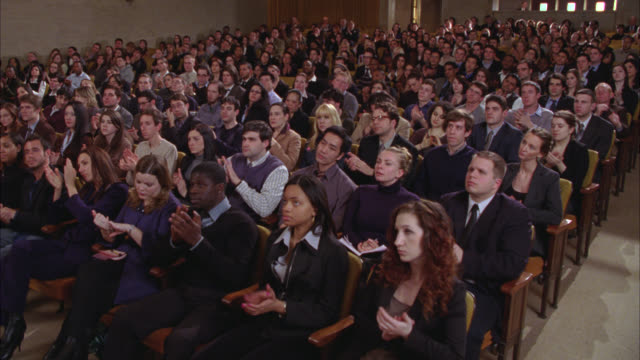 medium angle of crowd sitting in auditorium or theater. could be spectators. people clap. series. - auditorium stock videos and b-roll footage