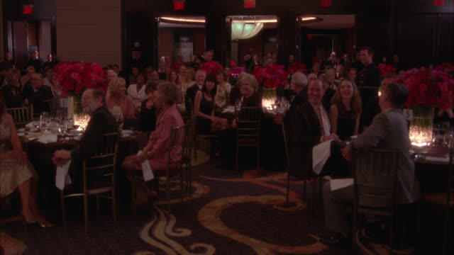 wide angle of people sitting at tables at upper class function. could be gala event, wedding, banquet, or party. tables decorated with roses. people clap. waiters walk around with trays. - banquet stock videos & royalty-free footage