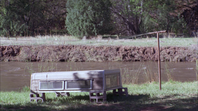 wide angle of old, abandoned, camper or trailer shell or cover sitting on cinder blocks in grass. river, stream or creek in bg. - camper trailer stock videos and b-roll footage