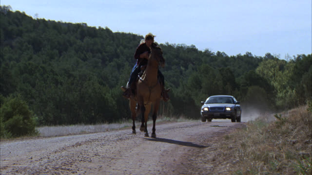 wide angle of man and woman on horse fleeing from car. could be dirt road or trail. could be country or rural area. man and woman ride into woods or forest area. car chases. stunts. animal stunts. horseback riding. - trail ride stock videos and b-roll footage