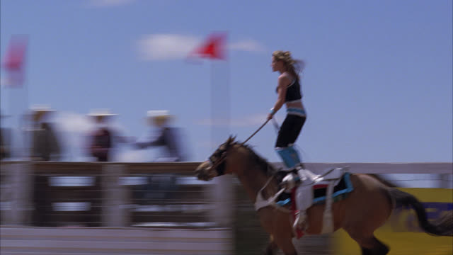 pan right to left following woman doing tricks while riding horseback. rodeo. stunts. western. crowd of people or spectators cheering, applauding or clapping. - rodeo stock videos & royalty-free footage