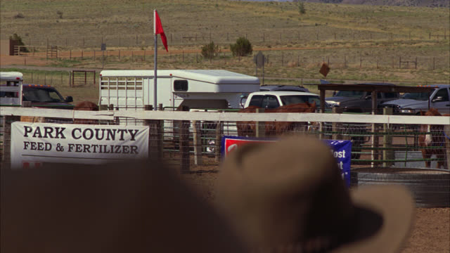 wide angle of female rodeo rider or performer doing acrobatics and stunts on horse. woman wears flashy costume. pen, arena, or enclosure. fence visible. people in cowboy hats watch. horse or animal trailers in bg. country or rural area. cowygirl. - animal pen stock videos & royalty-free footage