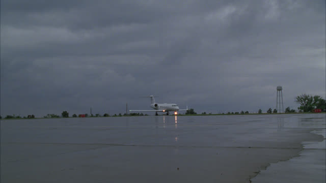vidéos et rushes de pan left to right following private or corporate airplane or jet taxiing on runway or tarmac of small town airport. overcast sky. water tower in bg. - piste d'envol