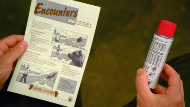 CLOSE ANGLE OF MAN'S HAND HOLDING PAMPHLET ABOUT BEAR ENCOUNTERS AND A CAN OF BEAR REPELLENT SPRAY. SERIES. COULD BE IN INFORMATION CENTER OF NATIONAL PARK.