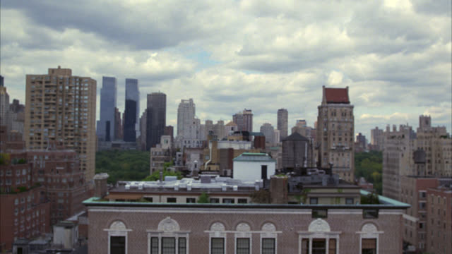 pan down from manhattan city skyline, pov from high rise office, apartment or condominium building on the upper west side to sidewalk and street below. time warner center towers or skyscrapers visible in bg. brick buildings. 48 fps. - entertainment center stock videos and b-roll footage