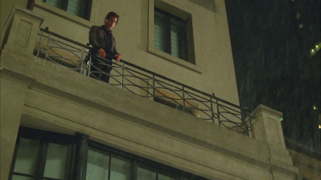 MEDIUM ANGLE OF MAN JUMPING OR FALLING FROM UPPER CLASS APARTMENT BUILDING BALCONY IN NEW YORK. STUNT. COULD BE SUICIDE OR MURDER. RAIN.
