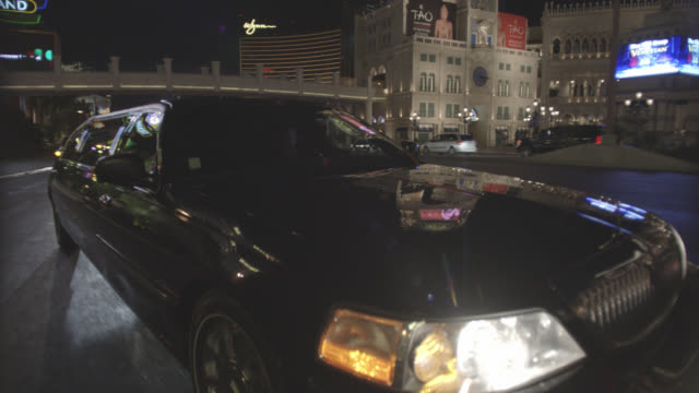wide angle moving pov 3/4 left back of limo driving along las vegas strip. lights from clubs, nightclubs, hotels, resorts, and casinos. palm trees. wynn, encore hotel. camera pulls up closer to passenger seat. chinese decorations on hotel. - limousine stock videos & royalty-free footage