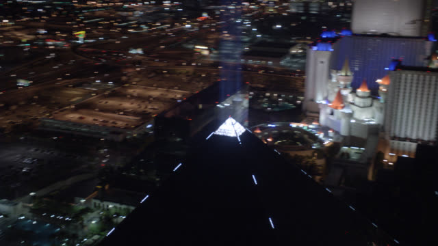 AERIAL OF VEGAS STRIP. CAMERA FOCUSES ON EXCALIBUR, CIRCLES AROUND LUXOR PYRAMID, AND FLOATS ABOVE STRIP TO NORTH. PROMINENT HOTELS AND CASINOS INCLUDE NEW YORK, NEW YORK, PLANET HOLLYWOOD, PARIS.